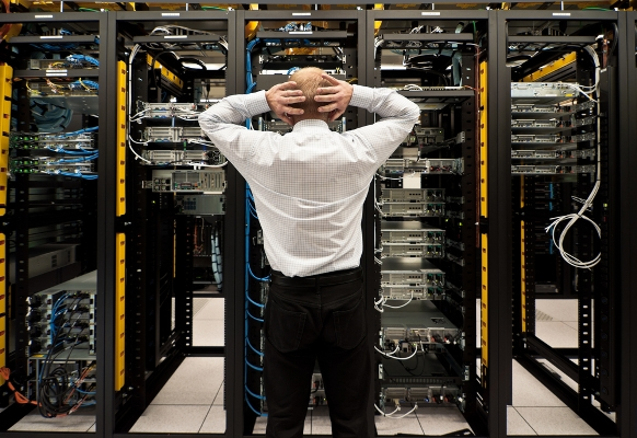 A stressed man sitting in a data center