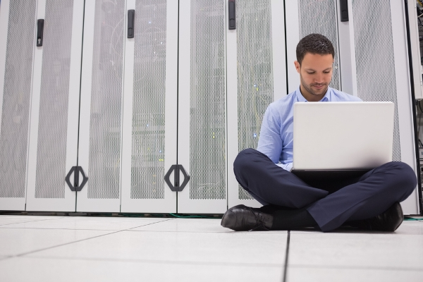 A man using a laptop while sitting in a data center
