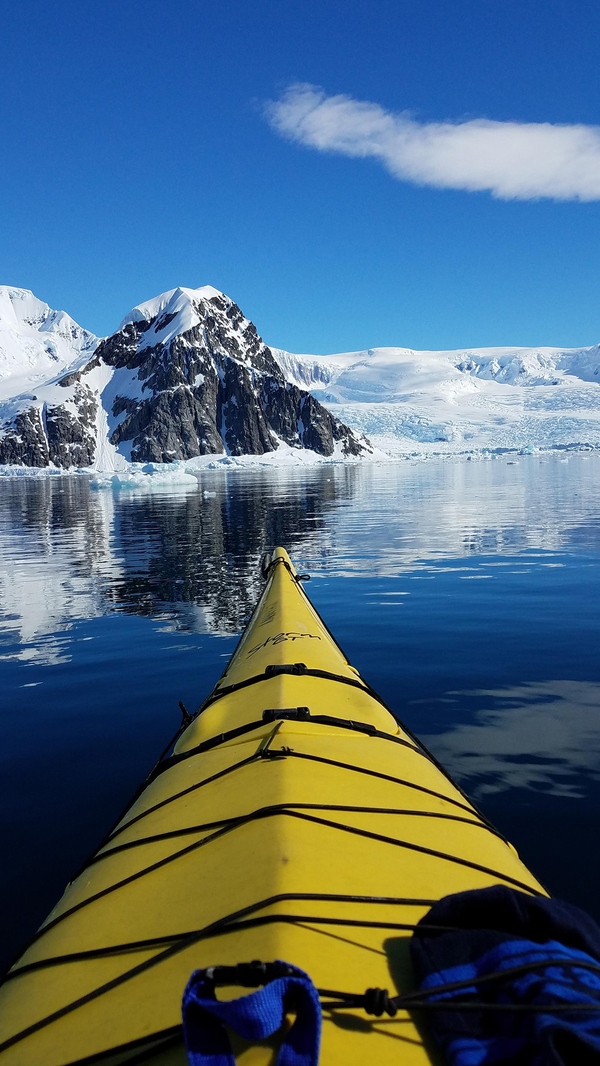 A Quark passenger enjoys the view from their kayak on tranquil Antarctic waters.