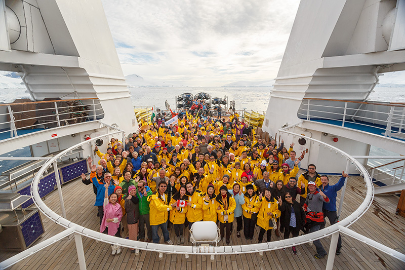 Passengers pose for photo on back deck of the ship