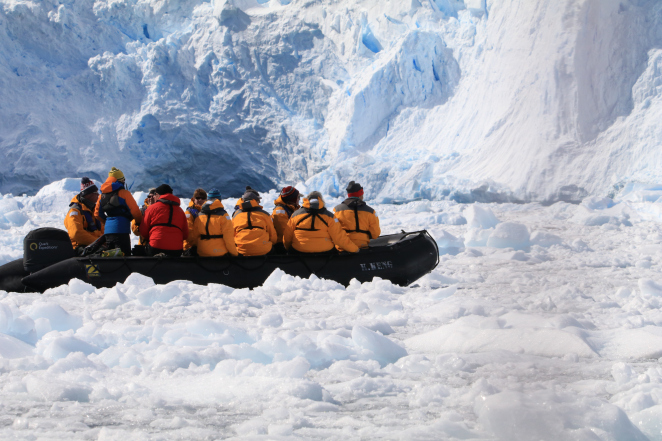 Quark Expeditions passengers zodiac cruise the ice-choked waters of Cierva Cove, beneath sprawling icebergs.