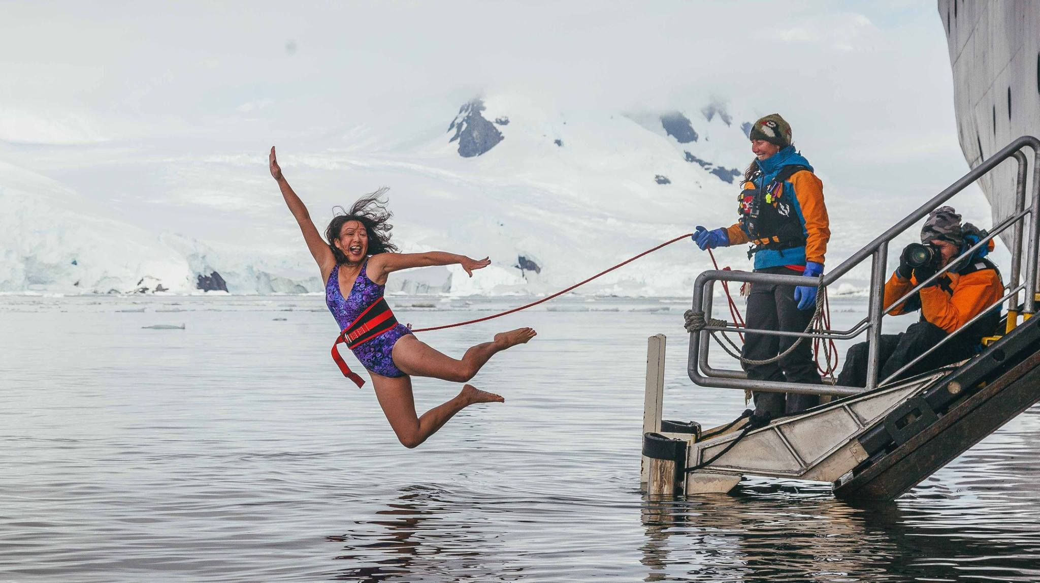 May Lee soars off the gangplank into an icy Antarctic bay during the Polar Plunge, a popular rite of passage on polar expeditions