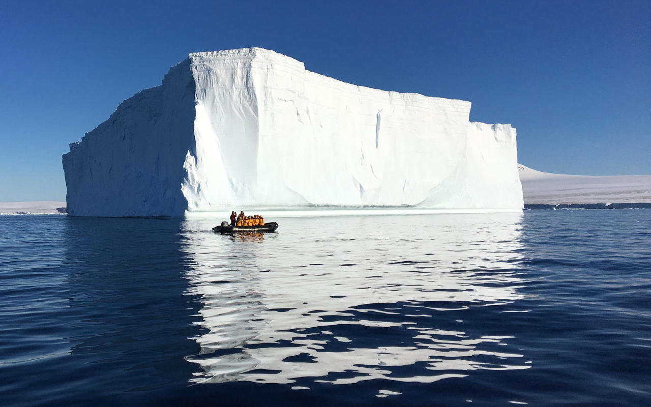 Zodiac cruising back to ship with a giant iceberg in the background