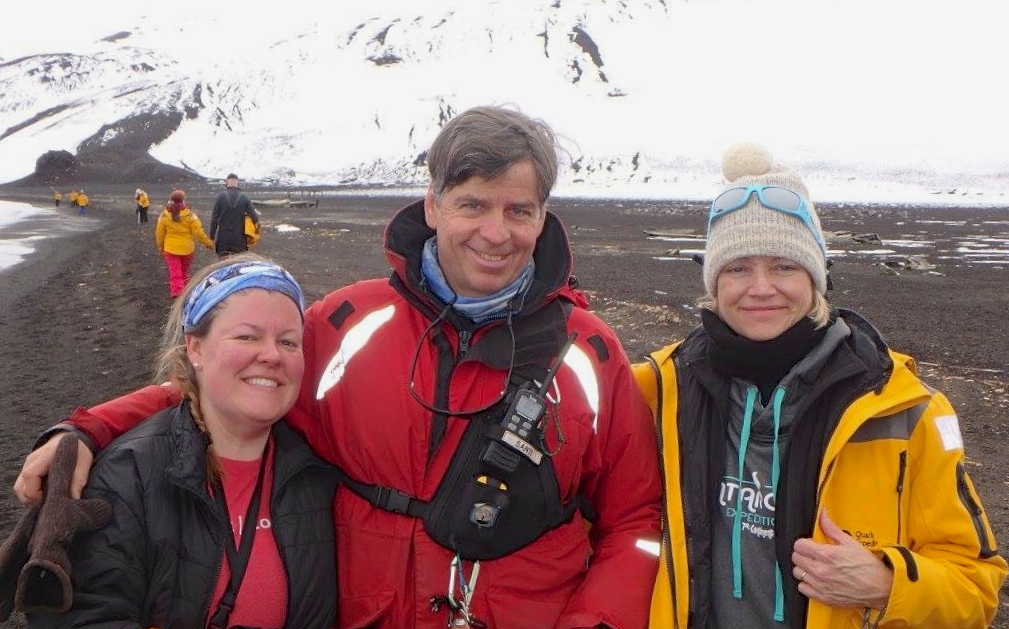 Passenger Bethany Eighmy, Quark Expeditions team member/ornithologist Santiago de la Vega, and passenger Kim Eighmy hiking and exploring Antarctica on a shore landing.