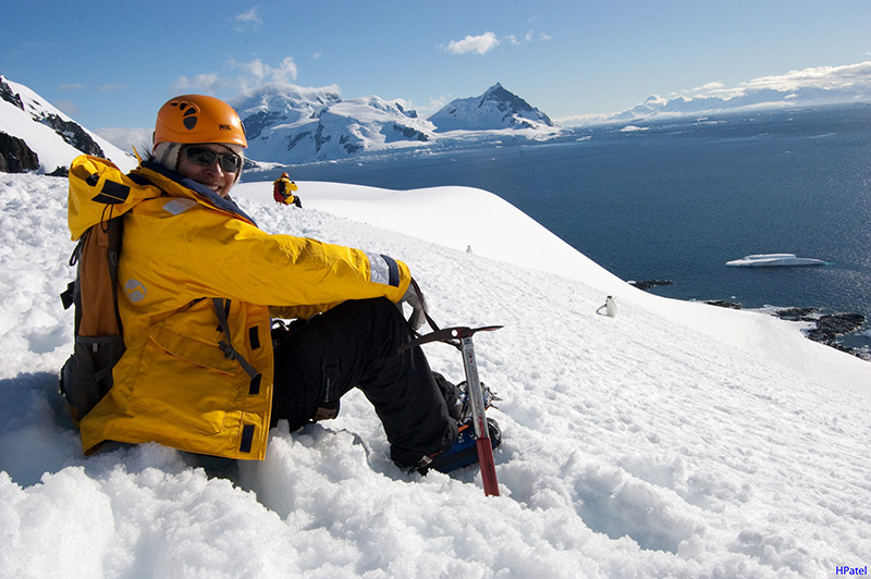 A passenger stops to enjoy the view on a mountaineering outing, while penguins march by just below. Photo: H. Patel