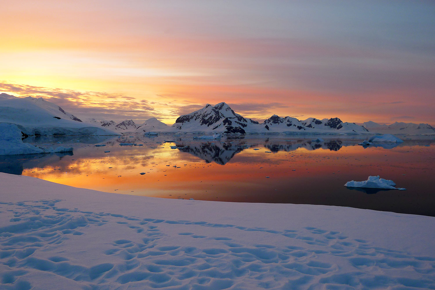 The sun sets over Leith Cove, Antarctica, setting the sky alight with spectacular hues of pink, orange and red.