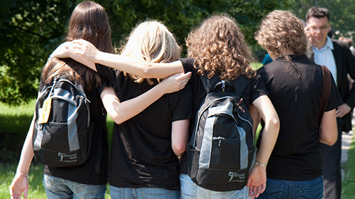 Four students with Encore Tours backpacks on walk down a sidewalk, surrounded by green trees