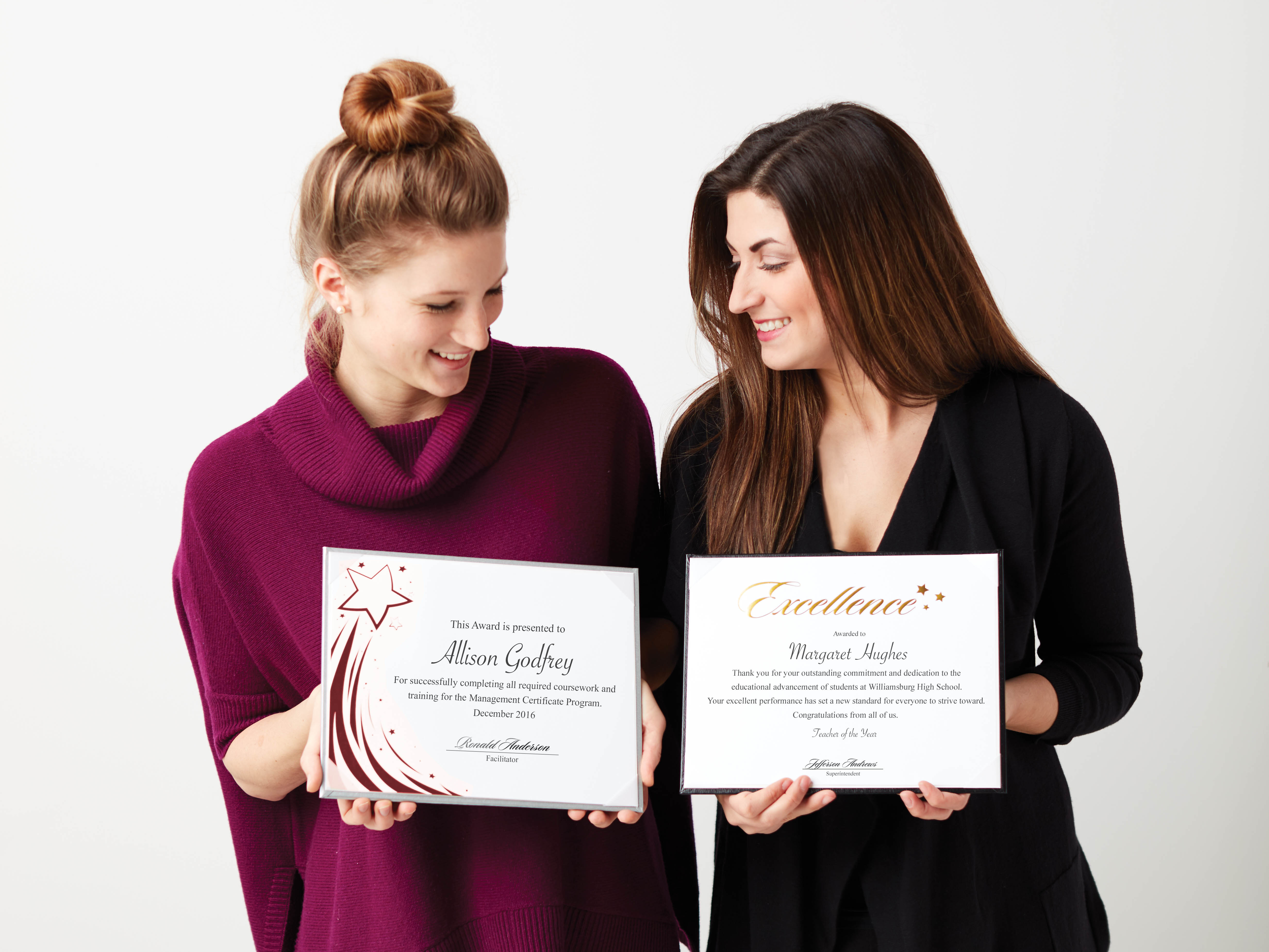 Two Young Women Holding Gold Foil Certificate Papers in Frames